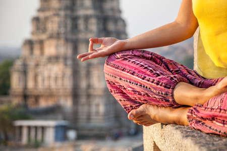 Mujer que hace la meditación cerca del templo de Virupaksha en Hampi, Karnataka, India