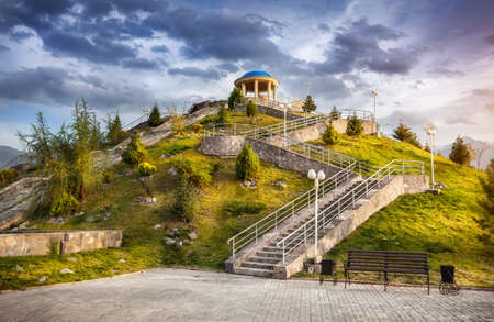Hill with Monument on the top with stairs and decorative plants at blue sky in dendra park of first president in Almaty, Kazakhstan
