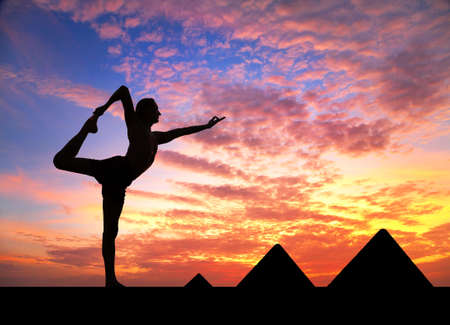 Man doing yoga at Egyptian Pyramids background in silhouettes photo