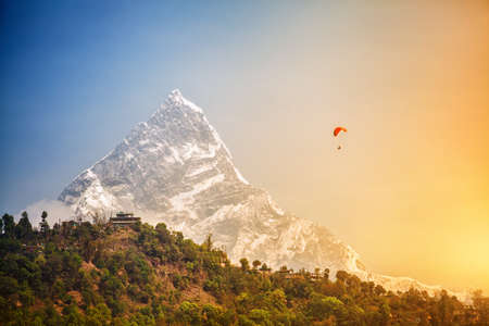 Paragliding near Machhapuchhre mount in Pokhara, Nepal Stock Photo