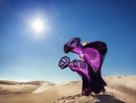 gipsy: Woman in violet skirt dancing in the desert at blue sky Stock Photo