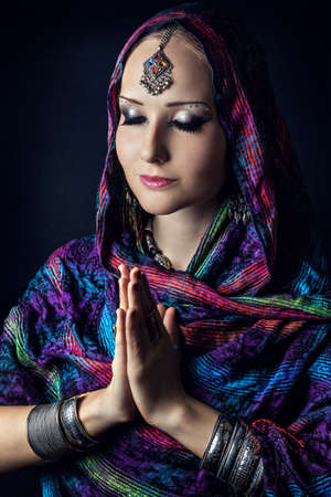 indian yoga: Woman with Indian tikka wrapped in scarf doing Namaste mudra at dark background
