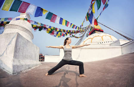 bodnath: Woman doing yoga warrior pose at Bodnath stupa, Kathmandu, Nepal
