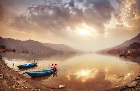 tal: POKHARA, NEPAL - APRIL 15, 2014: Nepalese children sitting in blue wooden boat on the shore of Fewa Tal at sunset cloudy sky