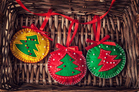 Christmas handmade red, yellow, green balls with tree from felt in brown twiggen basket photo