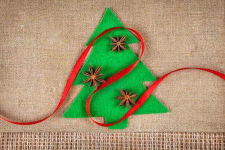 badiane: Christmas tree from felt with star anise and red ribbon on brown sackcloth