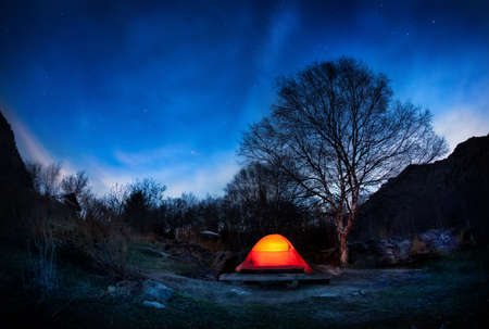 Orange tent in the mountain valley at blue night sky with stars in Kazakhstan