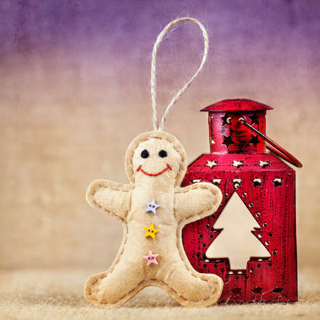 Gingerbread toy from felt near the red lantern with Christmas tree Stock Photo