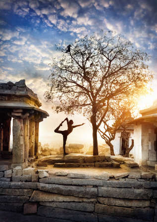ancient yoga: Man doing yoga near ancient ruins on Hemakuta hill in Hampi, Karnataka, India
