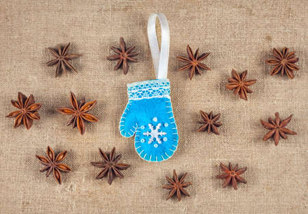 Blue handmade mitten from felt with snowflake and star anise nearby on textured sackcloth photo