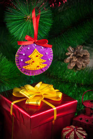 Christmas ball with tree from felt near the red box with yellow bow photo