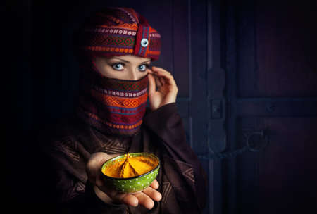 paranja: Oriental woman in turban offering yellow spice turmeric powder at bazar