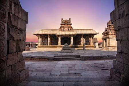 Ancient temple with columns at violet sky in Hampi, Karnataka, India