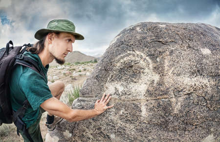 issyk kul: Man in hat with backpack touching the stone with ancient petroglyph of goat