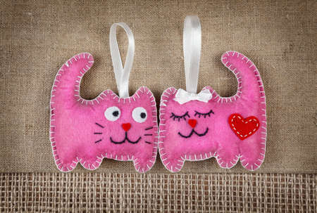 animal lover: Funny pink cats from felt in love on brown sackcloth Stock Photo
