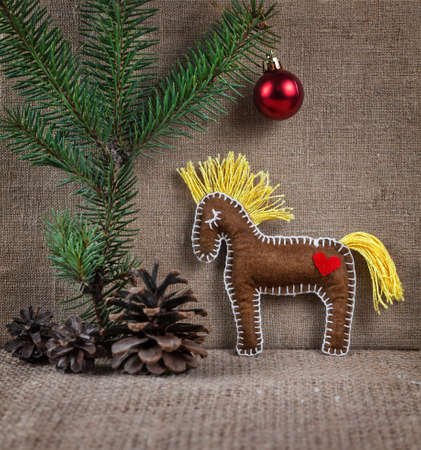 Horse toy from felt near Christmas tree with red ball and cones photo