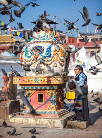 bodnath: BODNATH, KATHMANDU, NEPAL - APRIL 8, 2014: Tibetan old woman praying near Buddhist temple around flying doves near Bodnath stupa
