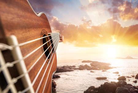 海の夕日を背景にギター ・ プレーヤー