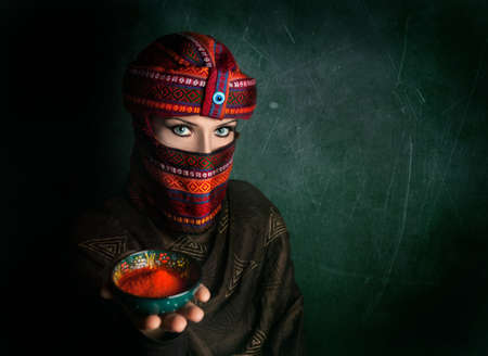 paranja: Oriental woman in turban offering red chili powder at green textured wall Stock Photo