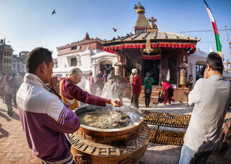 BODNATH, KATHMANDU, NEPAL - APRIL 8, 2014: People praying near tank with smoke at Bodnath stupa complex