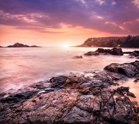 Sea with rocks at violet sunset sky in Om beach, Gokarna, Karnataka, India