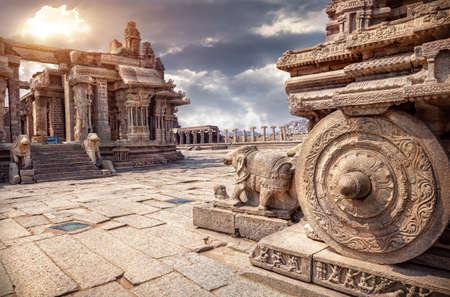 Steen strijdwagen in binnenplaats van Vittala tempel bij zons ondergang bewolkte hemel in Hampi, Karnataka, India