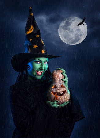sabbath: Witch with green skin holding carved Halloween pumpkin at moon and dark sky with rain Stock Photo