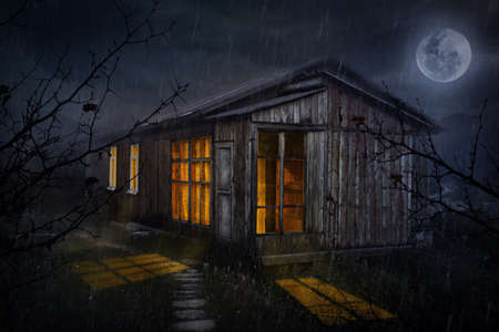달과 밤하늘에 빛나는 창문이있는 시골 집 스톡 콘텐츠
