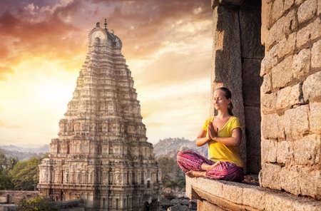 Vrouw met Namaste mudra zitten in de buurt Virupaksha tempel in Hampi, Karnataka, India