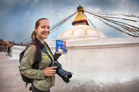 bodnath: BODNATH, KATHMANDU, NEPAL - APRIL 6, 2014: Foreign woman photographer with Lonely Planet guide book near Bodnath stupa, center of Buddhism pilgrimage
