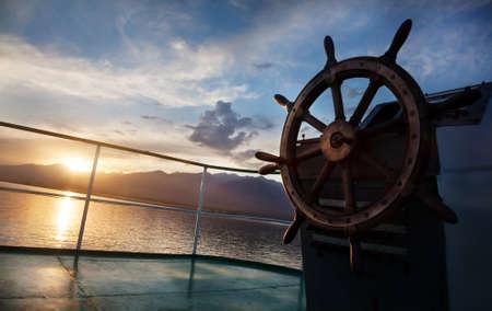 Houten wiel op het schip bij zonsondergang op Issyk Kul meer
