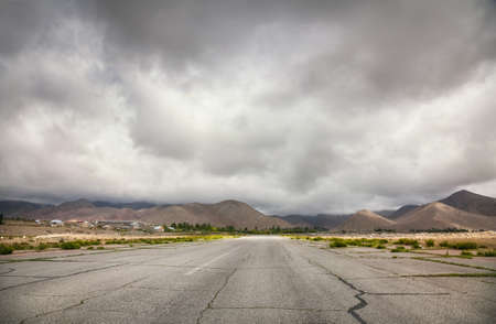 issyk kul: Wide road to the mountains at overcast sky in Cholpon Ata, Kyrgyzstan