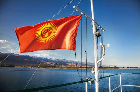 issyk kul: National Kyrgyzstan flag with shanirak and sun on the yacht on Issyk Kul lake