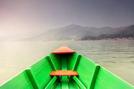 green boat: Wooden green boat floating on the Fewa Tal lake with view to Pokhara hills in Nepal