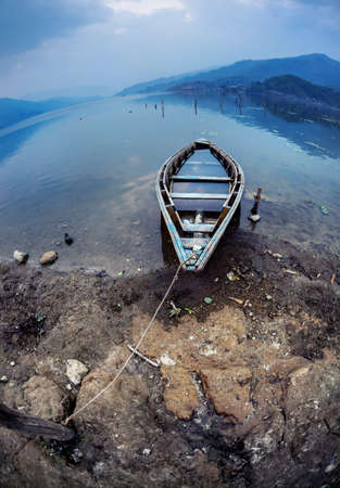 tal: Wooden flooded boat on the shore of Fewa Tal at overcast blue sky in Pokhara, Nepal