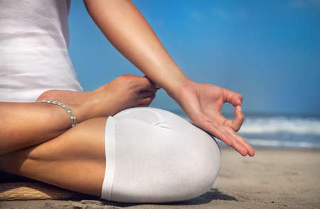 Woman doing yoga meditation in white costume on the beach in Goa, India