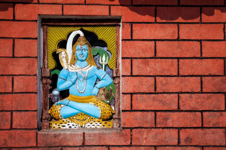 Shiva statue on brick wall in Hindu temple, Sarangkot, Nepal photo