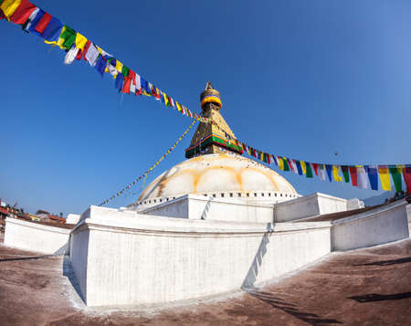 Bodhnath stupa with colorful prayer flags at blue sky in Kathmandu valley, Nepal photo
