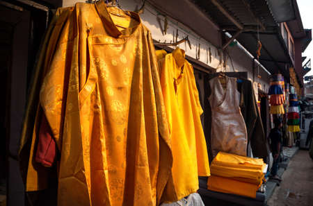 bodnath: Tibetan and Chinese yellow clothes from silk and cotton at the street shop near Boudhanath stupa in Kathmandu, Nepal Stock Photo