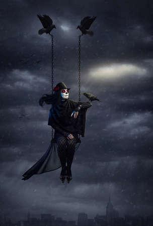 검은 까마귀를 들고와 폭설과 어두운 흐린 된 하늘에서 도시 위의 비행 설탕 두개골 메이크업을 가진 여자