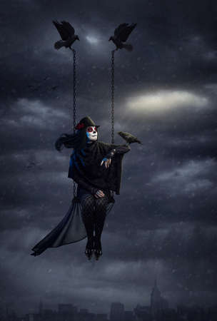 surreal: Woman with sugar skull makeup holding black crow and flying above the city at dark overcast sky with snowfall