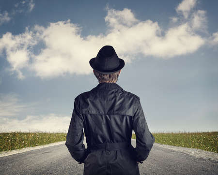 mystery man: Man in black hat on the road at blue cloudy sky background Stock Photo
