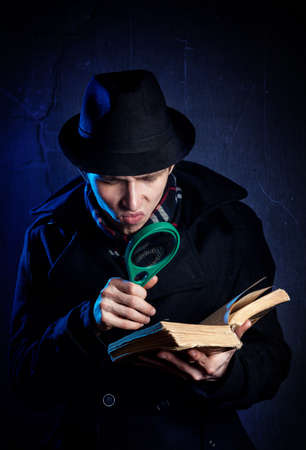 Man in black hat with magnifier glass reading the old book at dark background photo