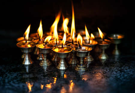 divali: Butter lamps with flames in the temple of Nepal