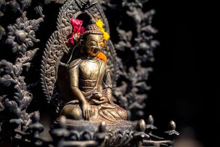 ネパール、パタン市の黄色と赤の花と仏像 写真素材