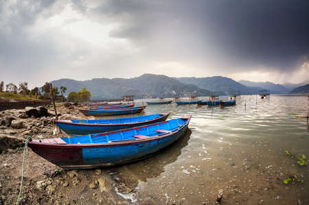 tal: Wooden blue boats on the shore of Fewa Tal at overcast rainy sky in Pokhara, Nepal