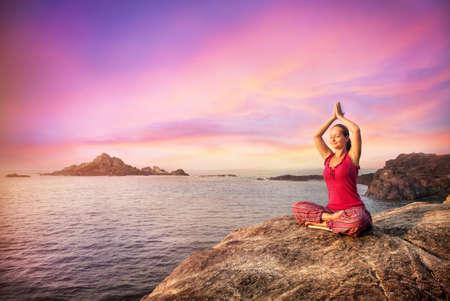 yoga sunset: Woman doing meditation in red costume on the stone near the ocean in Gokarna, Karnataka, India