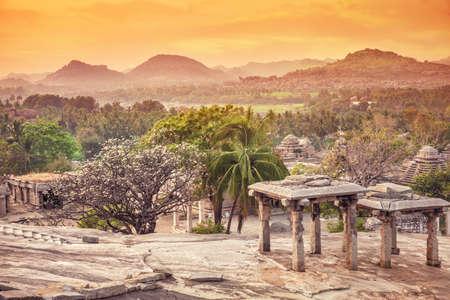 Ancient ruins on Hemakuta hill at orange sunset sky in Hampi, Karnataka, India