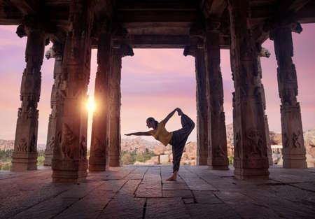 ancient yoga: Woman doing yoga in ruined ancient temple with columns, Hampi, Karnataka, India