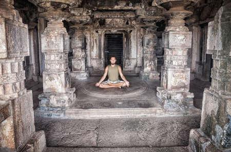 paz interior: Hombre que hace la meditación en el antiguo templo con tallado columnas en Hampi, Karnataka, India Foto de archivo